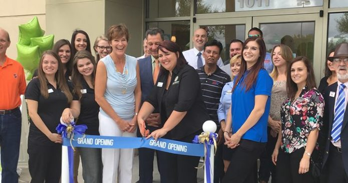 Brain Balance employees cutting ribbon in front of shop