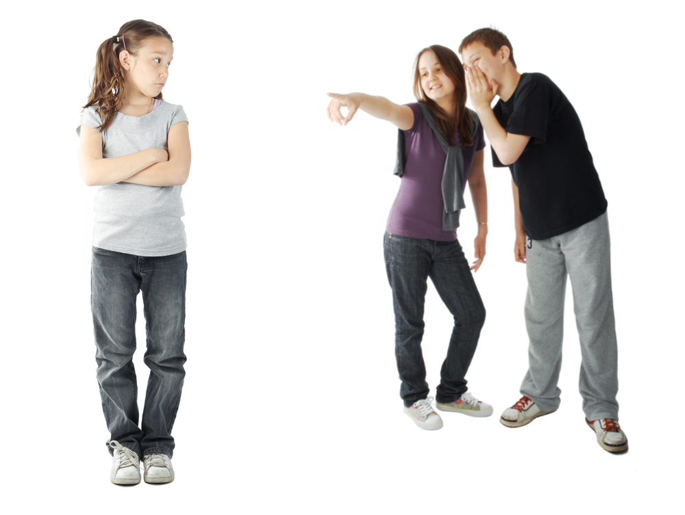 A young girl with arms folded is being made fun of by a boy and girl in the background.