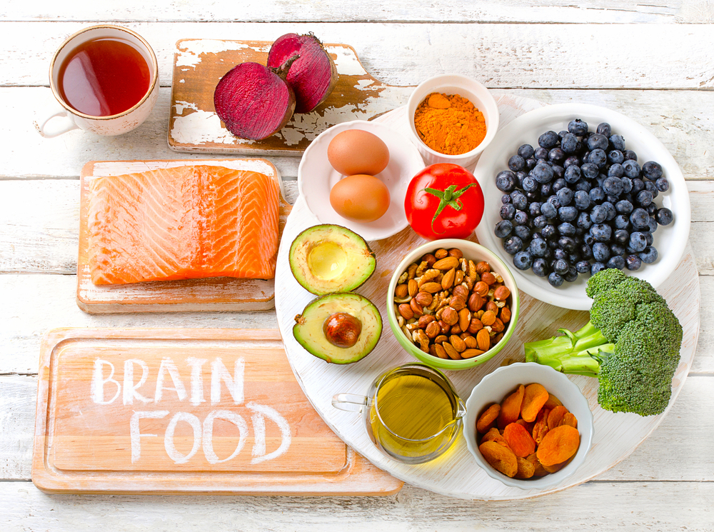 A platter of blueberries, broccoli, dried apricots, olive oil, avocado, eggs, turmeric, a tomato and almonds is next to a cutting board with the words Brain Food written on it. There is also a board with a raw slab of salmon, a board with a beet and a glass cup of tea.