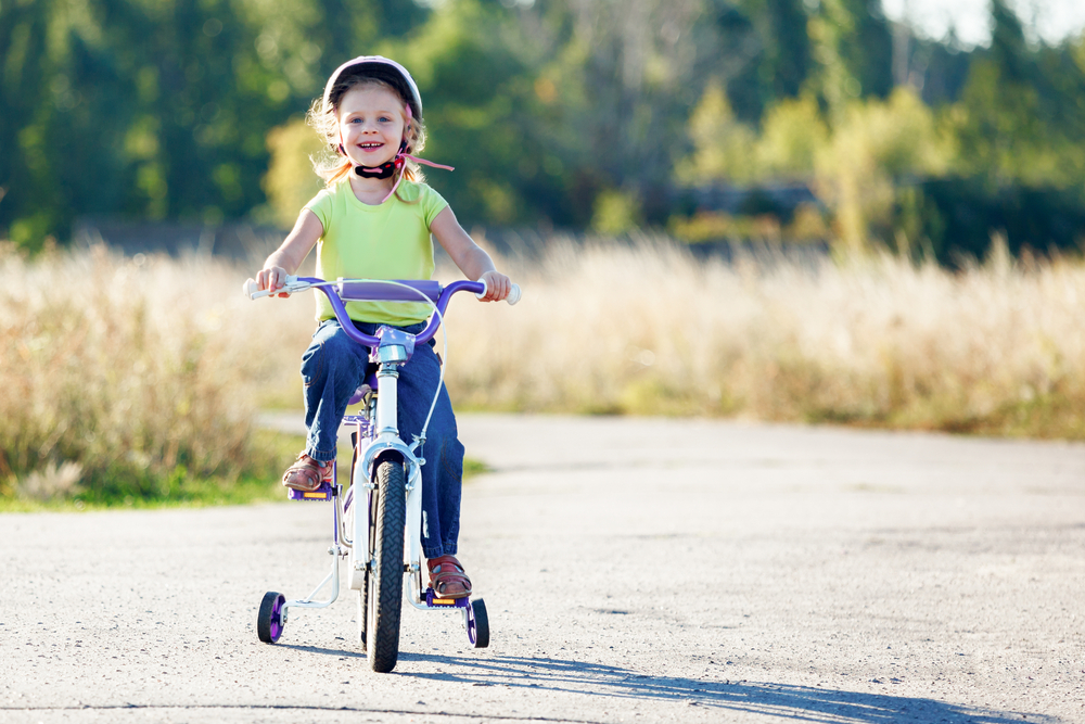A smiling little girl wearing a helmet, a green short-sleeved shirt, jeans and sandals rides a bike with training wheels on an unpaved road.