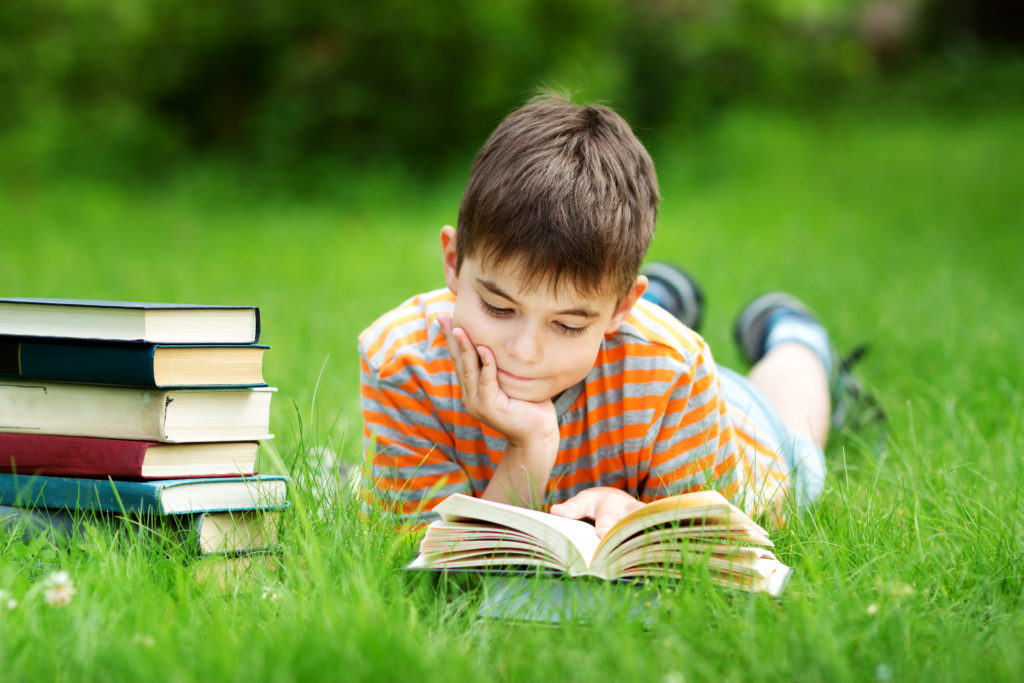 A boy of about 7 is on his stomach in the grass reading a book, with a stack of hard-back books in the grass to his right.
