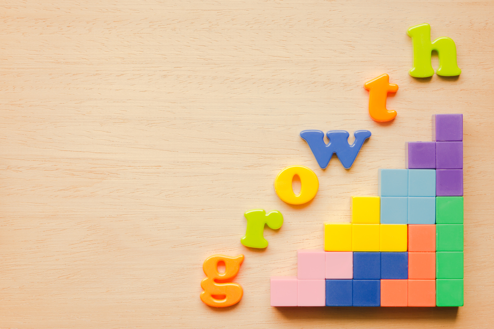 Letters spelling out the word growth follow an ascending grid of colored blocks on a wooden background.