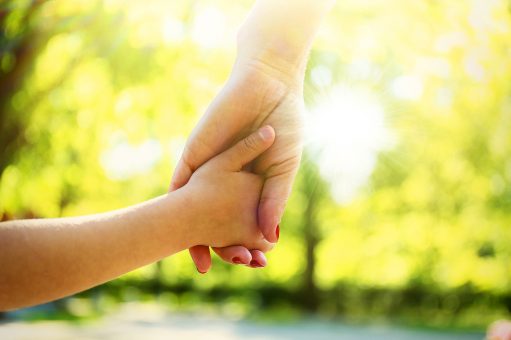 ALT: Close-up of a child holding a woman's hand as they walk through a sunny park.