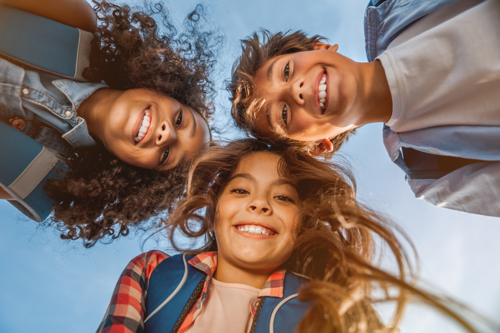Three smiling children stand in a circle and peer down into a camera, blue sky in the background.